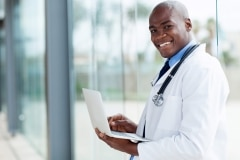 afro american doctor using laptop computer